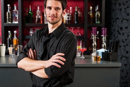 Barman in black standing at cocktail bar