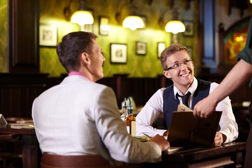 The waiter shows men in a pub menu